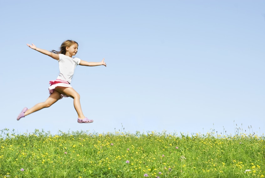 little girl jumping on meadow, she playing